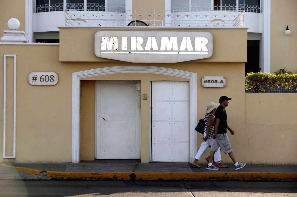 MAZATLAN, Jan 9, 2016 (Xinhua) -- File photo taken on July 12, 2015 shows people walking past the Miramar condominium, the site where Mexico's drug cartel kingpin Joaquin Guzman Loera was arrested during his previous escape from prison on Feb. 22, 20