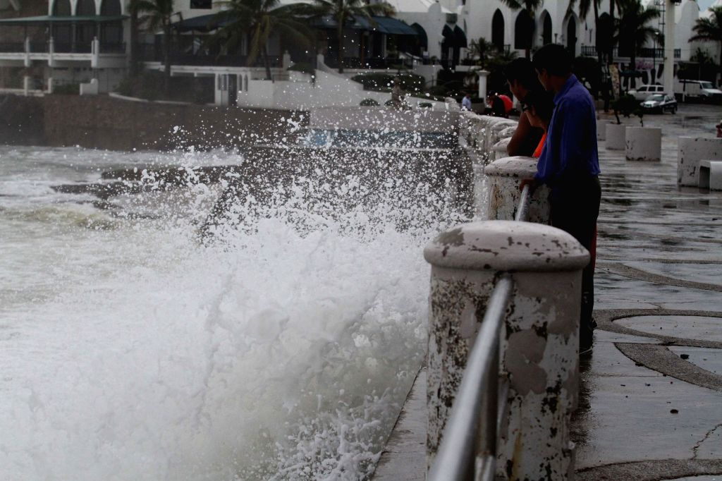 """People look the high waves caused by hurricane """"Norbert"""", in the boardwalk of Mazatlan Port, in Sinaloa State, northwest Mexico, on Sept. 4, 2014. ..."""