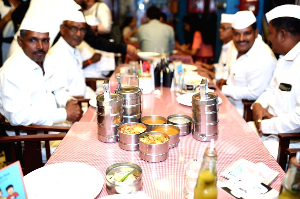 Meals being served in Dabbas to the Dabbawala community at restaurant chain SodaBottleOpenerWala.