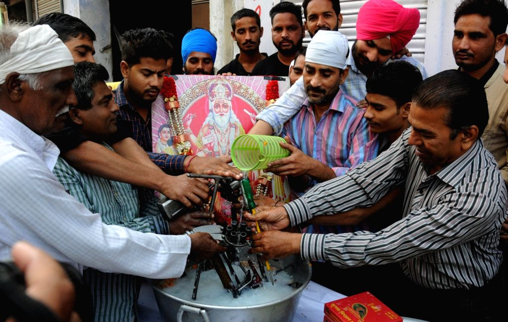 Mechanics wash their tools with milk on the occasion of 'Vishwakarma Puja' in Amritsar on Oct 31, 2016.