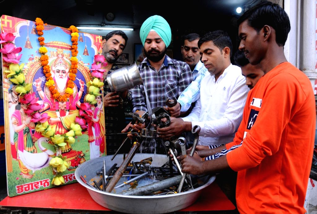 Mechanics wash their weapons as they perform rituals during Vishwakarma Puja in Amritsar, on Oct 28, 2019.