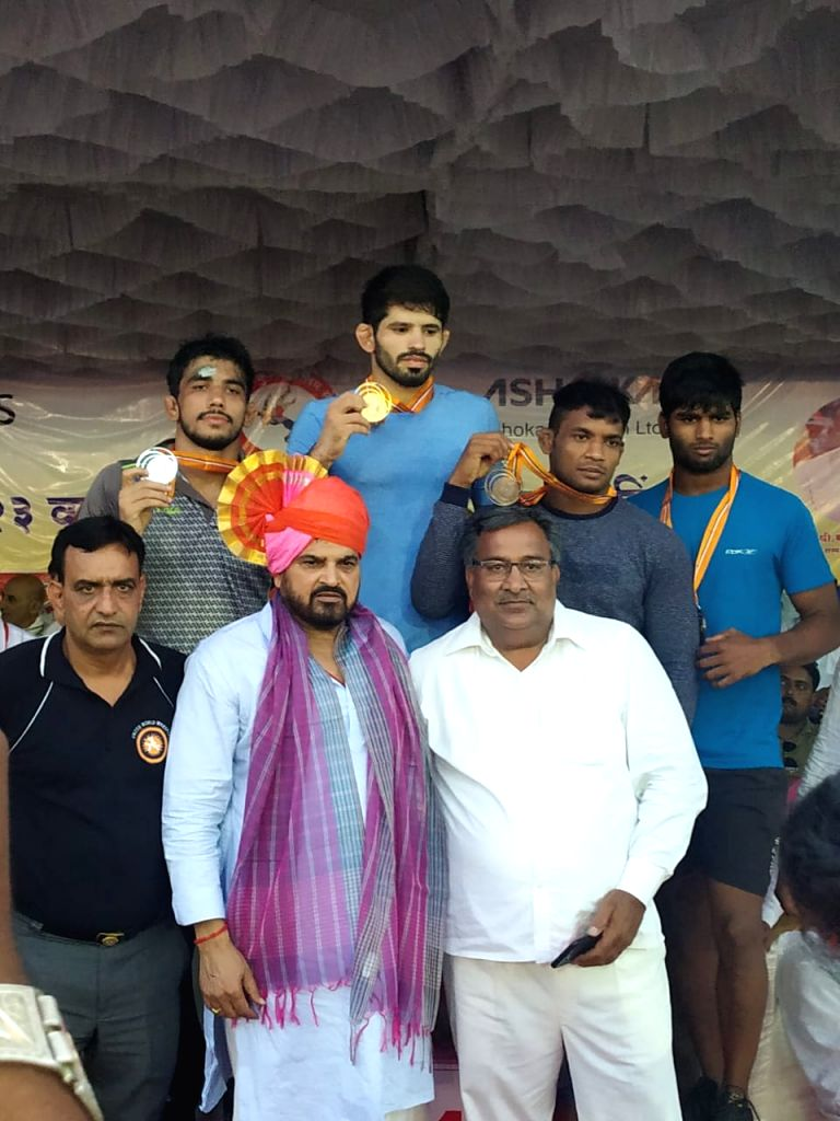 Medal winners in the 65 kg category pose with WFI President Brij Bhushan Sharan Singh (Center) on the first day of 2nd Tata Motors U-23 National Wrestling Championship in Shirdi, Maharashtra ...