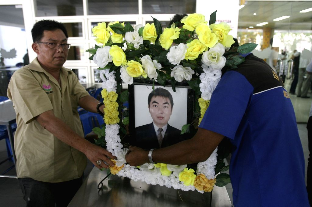 Relatives of Hendry, a victim of Malaysia Airlines flight MH-17, hold his picture as his body returns home in Medan, North Sumatra, Indonesia, Aug. 31, 2014. The ...