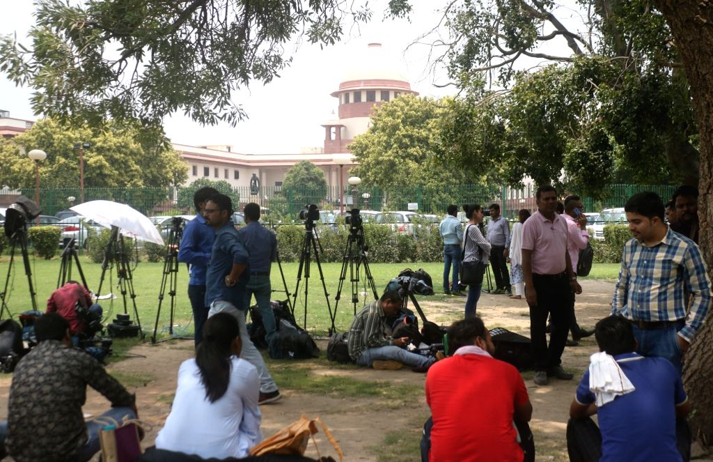 Media persons wait outside the Supreme court during the hearing on petitions against Section 377 of the Indian Penal Code that makes homosexuality a crime; in New Delhi on July 10, 2018.