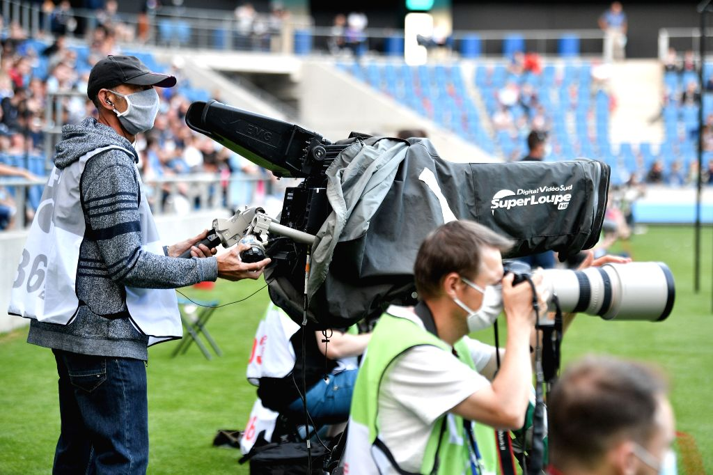 Media staff wearing masks work on the field during a friendly football match between Paris Saint Germain and Le Havre at the Ocean Stadium in Le Havre, France, ...