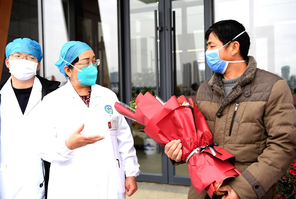 Medical staff members give flowers to a patient to congratulate his cure at the First Affiliated Hospital of Nanchang University in Nanchang, east China's Jiangxi ...
