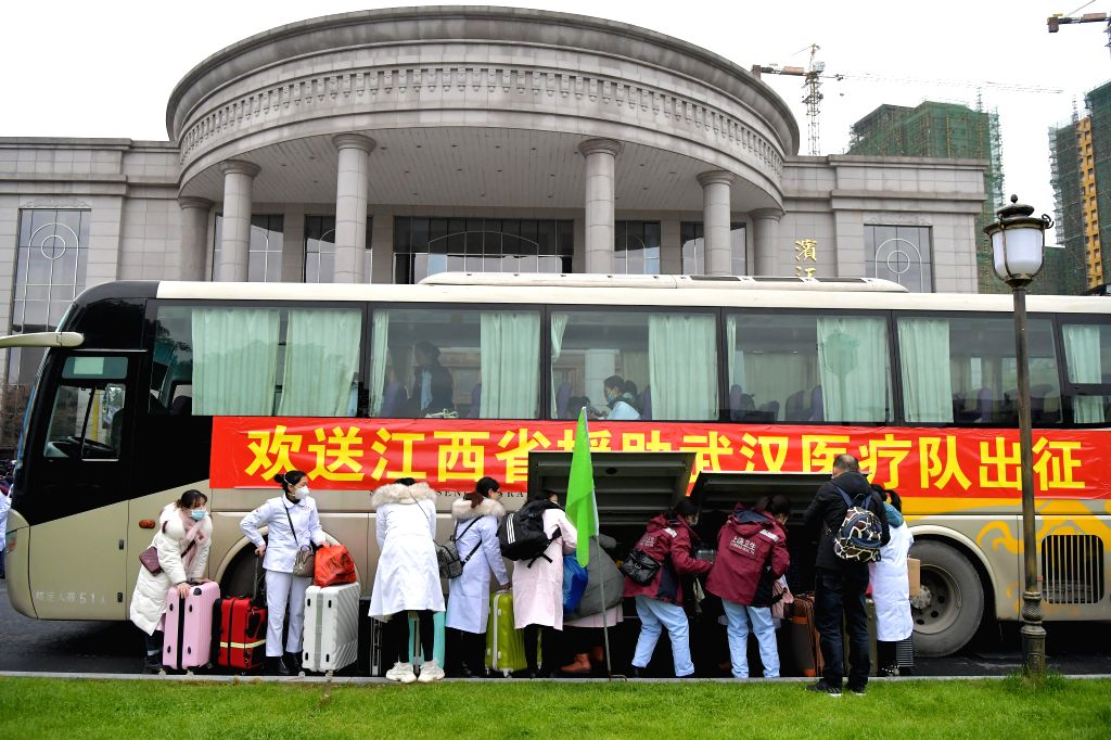 Medical staff members load luggages on a bus before heading for Wuhan of Hubei Province in Nanchang, east China's Jiangxi Province, Jan. 27, 2020. A team comprised ...