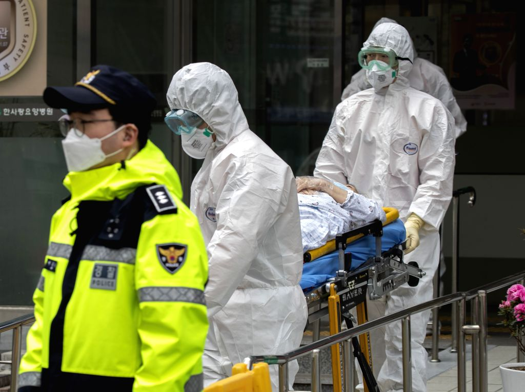 Medical staff transport patients of a sanatorium where mass coronavirus infections occurred to hospital in Daegu, South Korea, March 19, 2020. South Korea reported ...