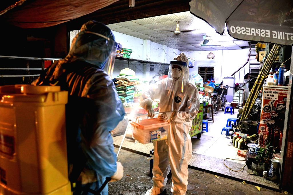 Medical workers conduct disinfection in an alley where a suspected COVID-19 patient lives, in Hanoi, Vietnam, on July 29, 2020. Vietnam reported 12 new cases of ...
