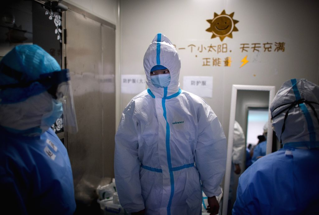 Medical workers from east China's Zhejiang Province wear protective suits at the Wuhan pulmonary hospital in Wuhan, central China's Hubei Province, March 19, 2020. ...