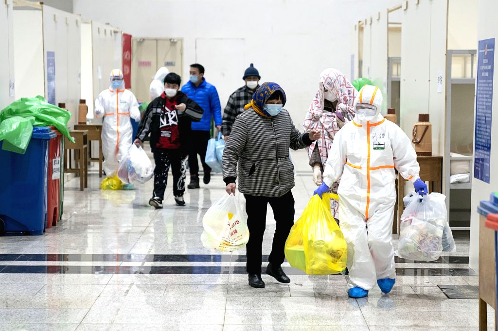 Medical workers help patients infected with the novel coronavirus check in at a makeshift hospital in Wuhan, central China's Hubei Province, Feb. 5, 2020. The first ...