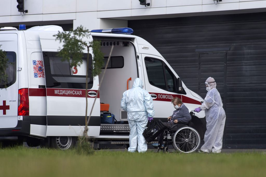 Medical workers wearing protective gear help a woman, suspected of contracting the coronavirus, get on a wheelchair at a hospital in Kommunarka, outside Moscow, ...