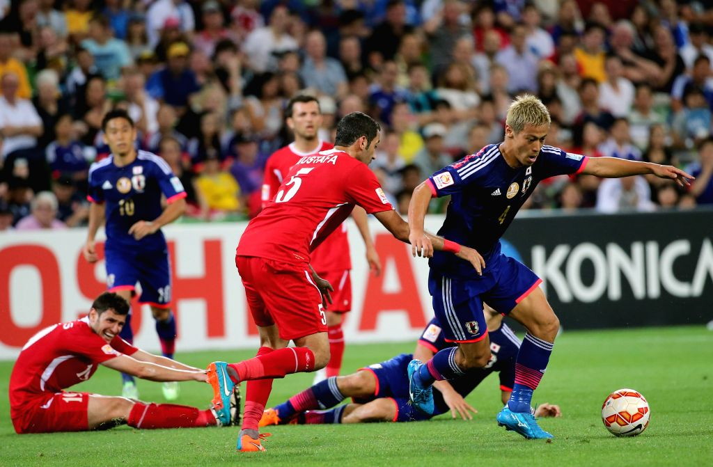 Japan's Keisuke Honda (R) fights for the ball during the third round match of Group D between Jordan and Japan at the 2015 AFC Asian Cup tournament in Melbourne, .