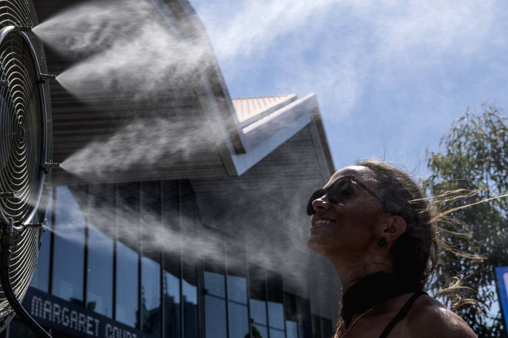 MELBOURNE, Jan. 24, 2019 - A spectator stands in front of a electric fan during the 2019 Australian Open in Melbourne, Australia, on Jan. 24, 2019. The Melbourne Park witnessed hot weather here on ...