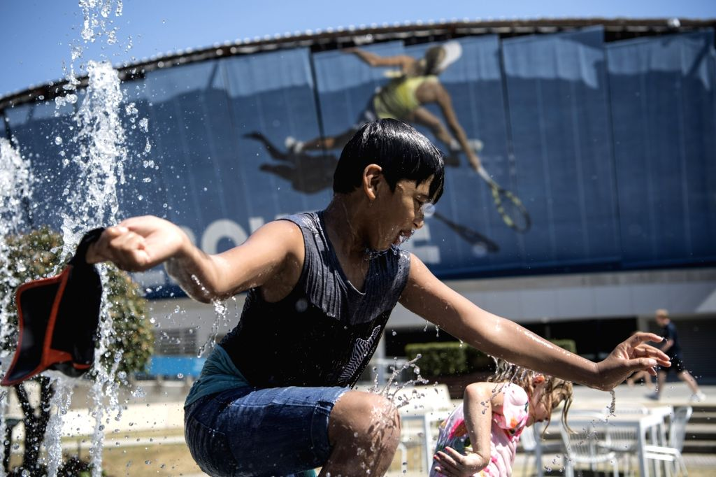 MELBOURNE, Jan. 24, 2019 - Spectators play at a fountain during the 2019 Australian Open in Melbourne, Australia, on Jan. 24, 2019. The Melbourne Park witnessed hot weather here on Thursday.
