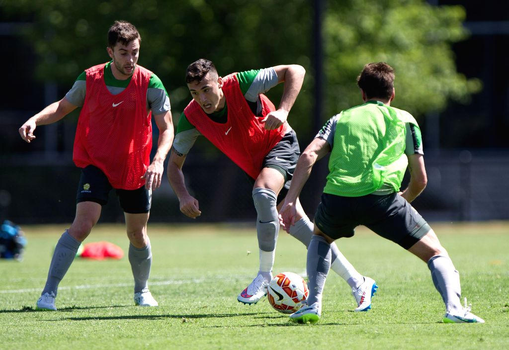 Socceroos players Jason Davidson (C) and Tommy Oar (L) vie for the ball during the team training session ahead of AFC Asian Cup at the Collingwood Training Centre,