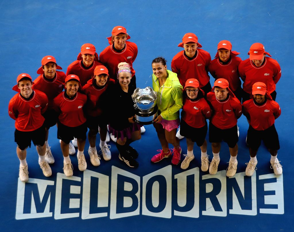 Bethanie Mattek-Sands (4th L, front) of the U.S.and Lucie Safarova (4th R, front) of the Czech Republic pose with volunteers after winning their women's doubles ..