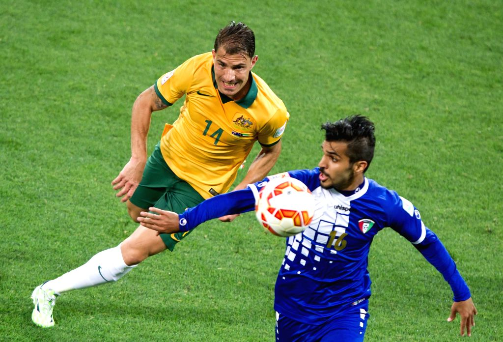 James Troisi (L) of Australia vies with Faisal Zayed Alharbi of Kuwait during the opening football match at the AFC Asian Cup in Melbourne, Australia, Jan. 9, ...