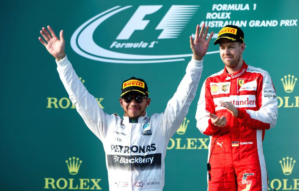 Scuderia Ferrari Formula One driver Sebastian Vettel of Germany reacts as Mercedes AMG Petronas Formula One driver Lewis Hamilton of Britain (L) celebrates after ...