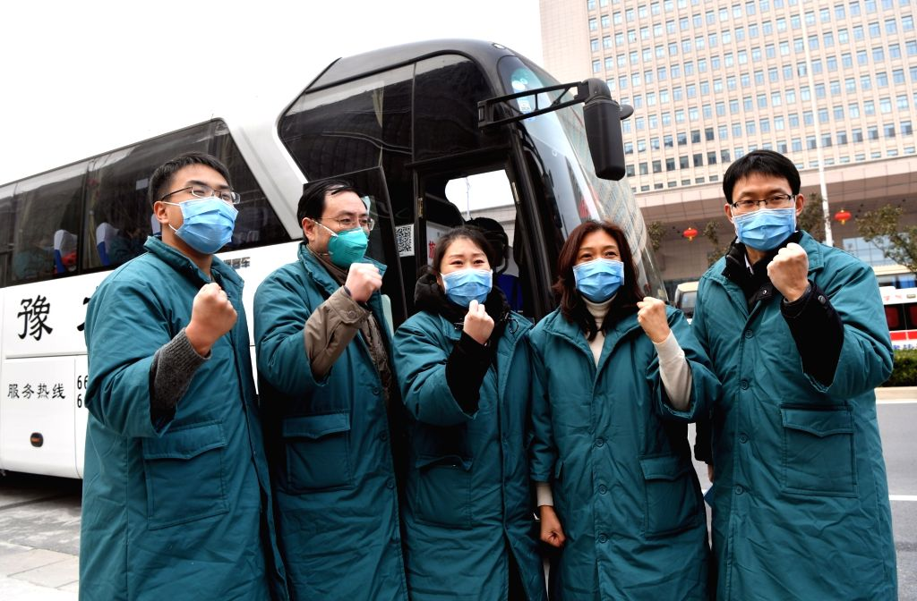 Members of a medical team pose for a group photo before their departure in Zhengzhou, central China's Henan Province, on Jan. 26, 2020. A team comprised of 137 ...