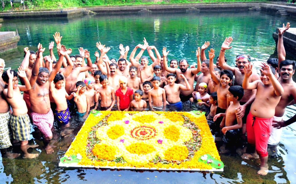 Members of a swimmers' club make a flower carpet as a part of Onam celebrations on a pond at Pallikunnu in Kannur, Kerala on Sept 11. 2016.