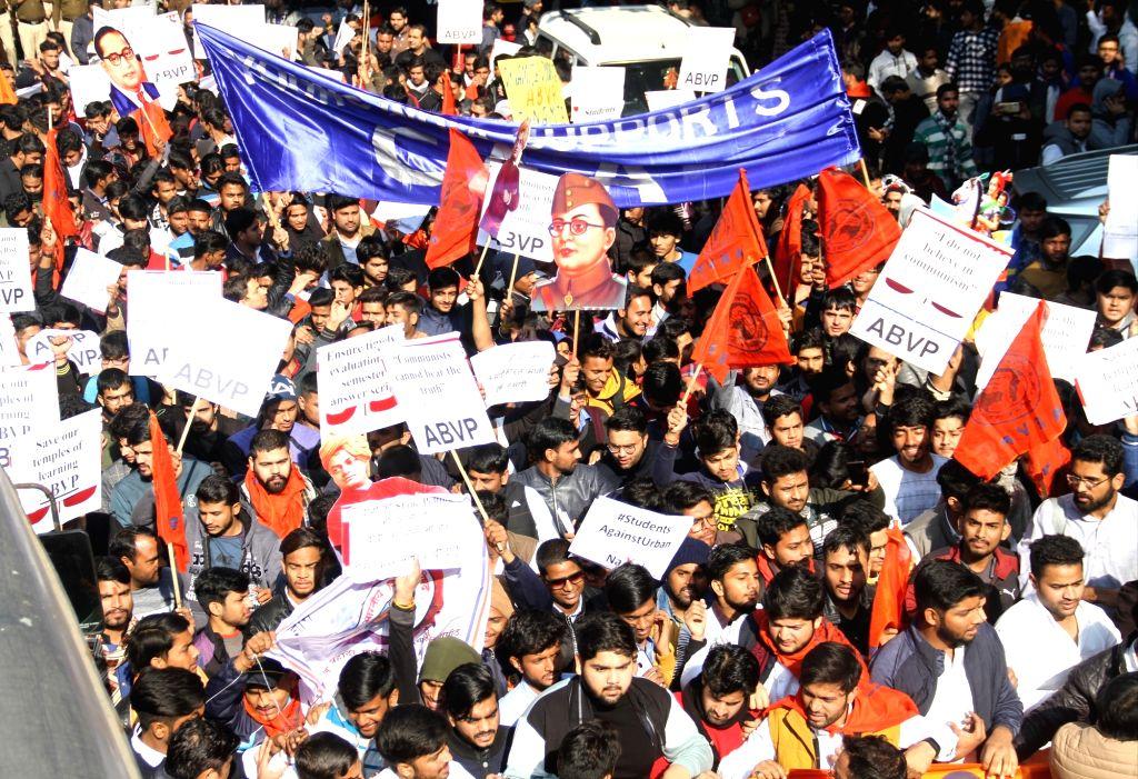 Members of Akhil Bharatiya Vidyarthi Parishad (ABVP) participate in a march supporting the Citizenship Amendment Act (CAA) 2019 and denouncing JNU violence, at Delhi University on Jan 11, ...