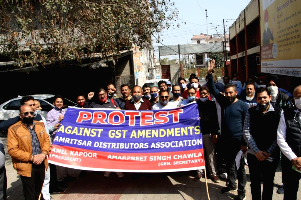 Members of Amritsar distributors association protest against gst amendments at dc office in Amritsar.