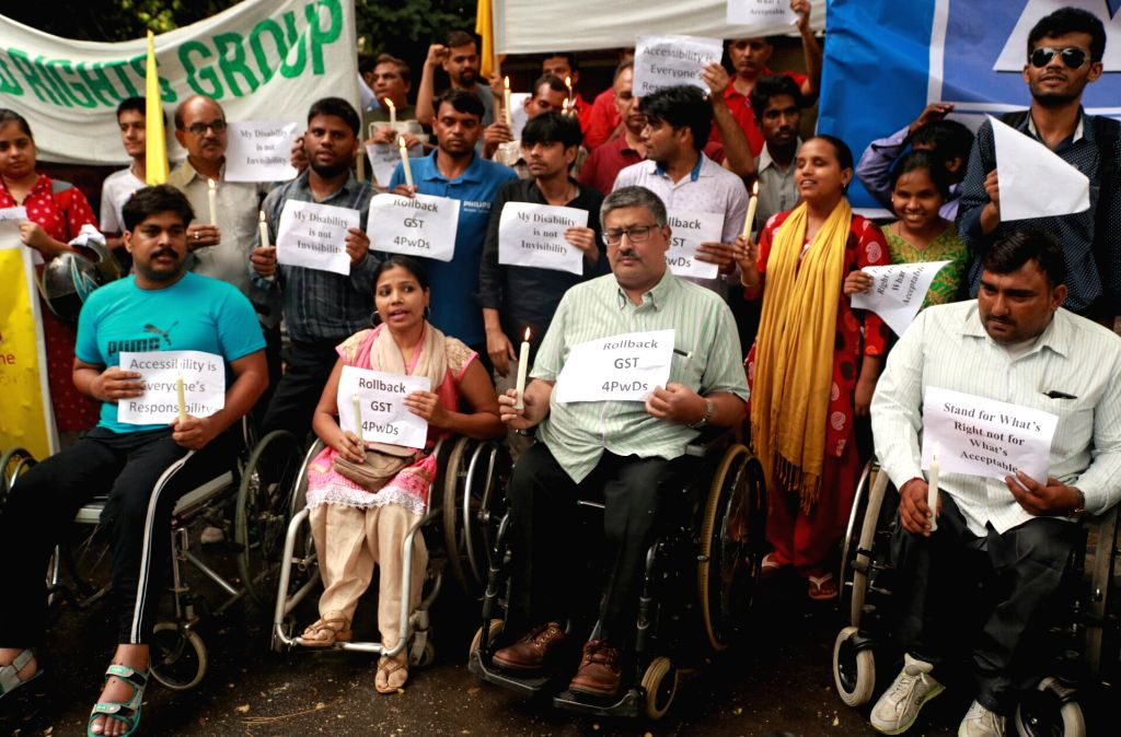 Members of Disability Rights Group (DRG) participate in a candle light vigil against GST on disability aids and appliances at Jantar Mantar in New Delhi, on June 30, 2017.