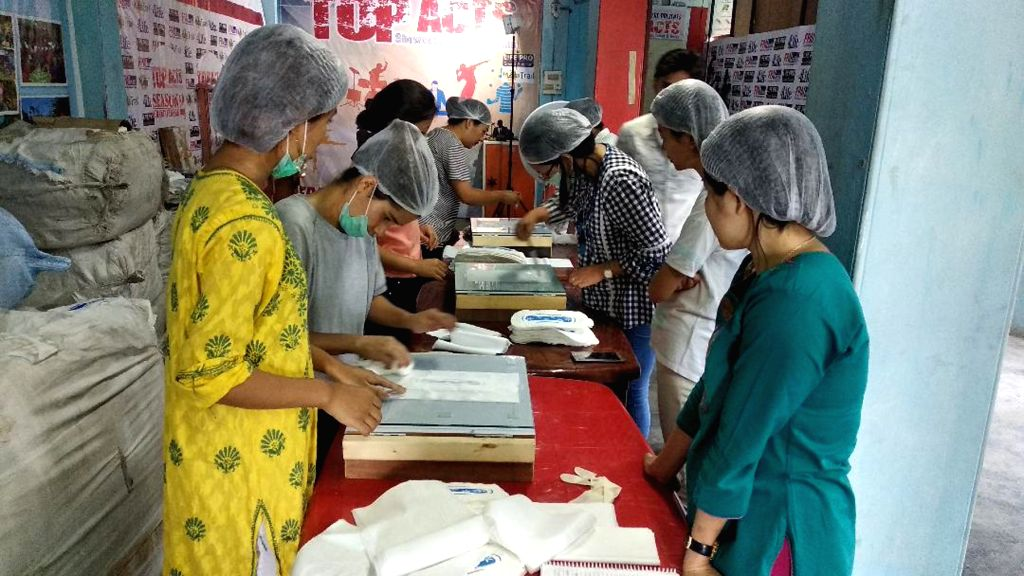Members of Family Planning Association of India, Nagaland busy making sanitary napkins using its first ever sanitary napkin making machine installed after they were imparted two-day training ...