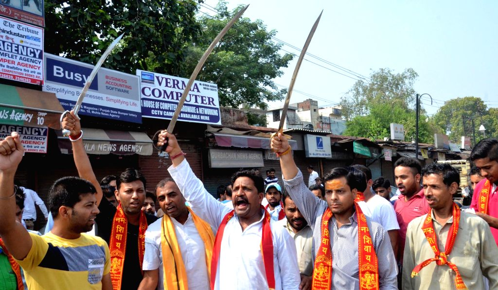 Members of Hindu organisations brandishing swords stage a demonstration on Amritsar streets on July 21, 2014.