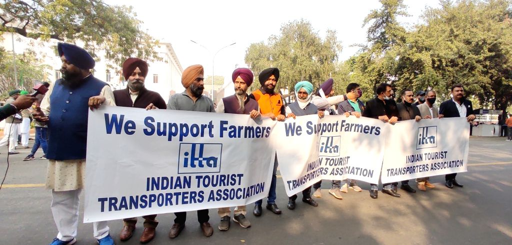 Members of Indian Tourist Transporters Association stand in support of farmers at Vigyan Bhawan as farmer leaders arrived to hold the fifth round of talks with the Centre even as the ...