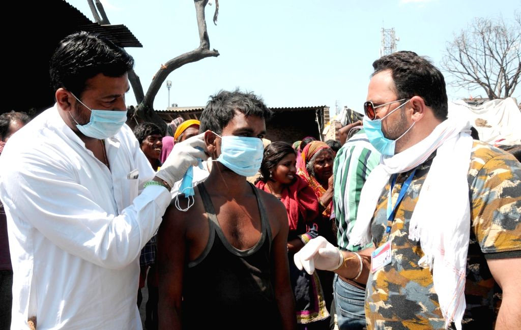 Members of International Human Rights & Crime Control Organization (IHRCC) distribute masks among slum dwellers in Amritsar during the extended nationwide lockdown imposed to mitigate ...