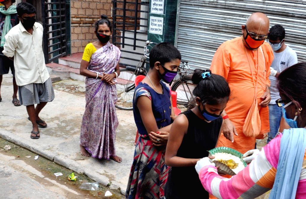 Members of ISKCON temple distribute free foods among the poor, needy and homeless people during the extended nationwide lockdown imposed to mitigate the spread of coronavirus, in Kolkata on ...