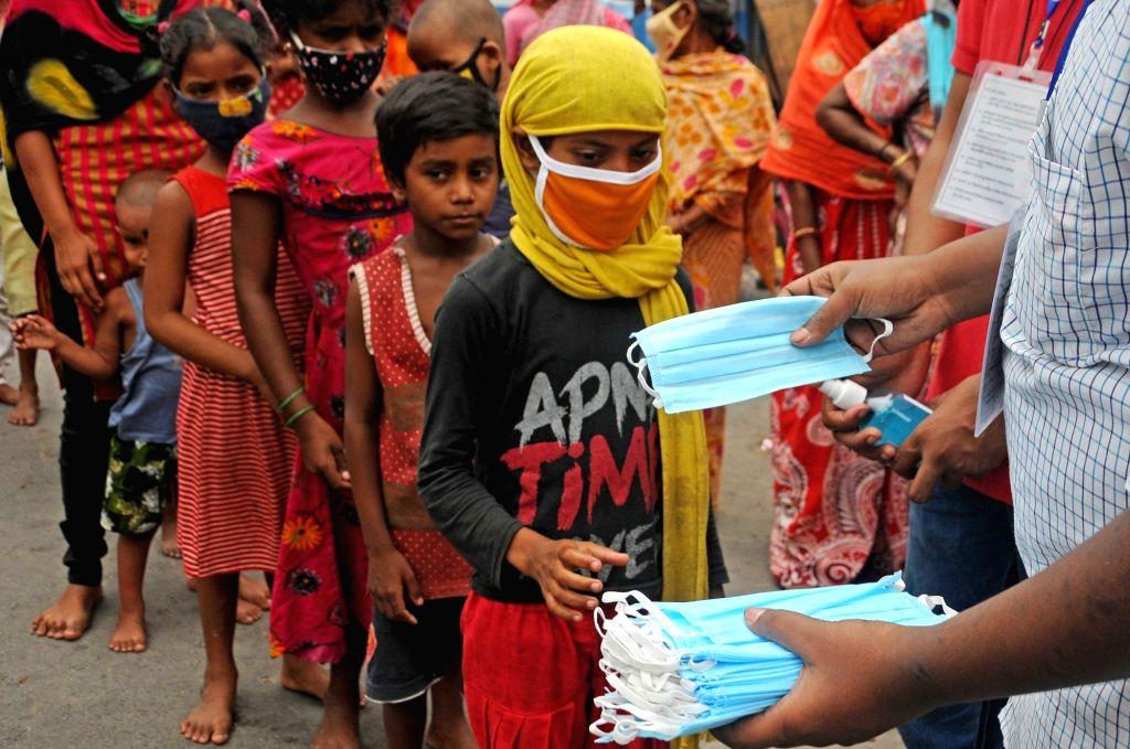 Members of Jeevan Jyoti Foundation distribute masks, sanitizer to poor children and people at Bidhannagar colony area during lockdown on Coronavirus pandemic in Kolkata on Tuesday, 25 May, ...