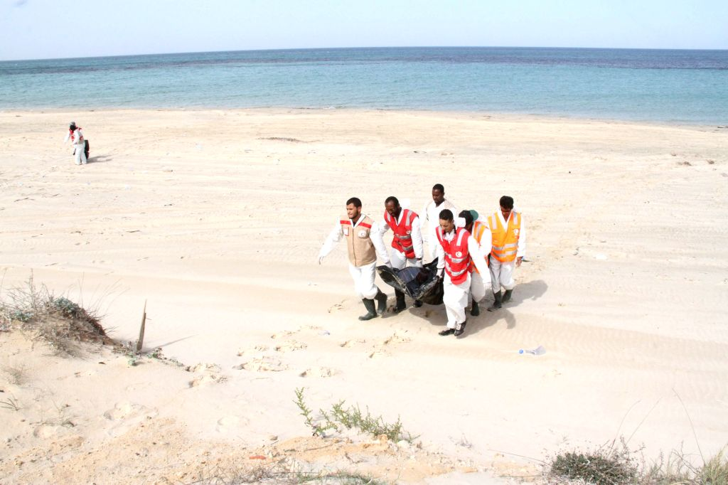 Members of Libyan Red Crescent remove a body from a beach in coastal Libyan town of Guarabouli, 60km east of the capital Tripoli, Libya, on Oct. 21, 2015. Six ...