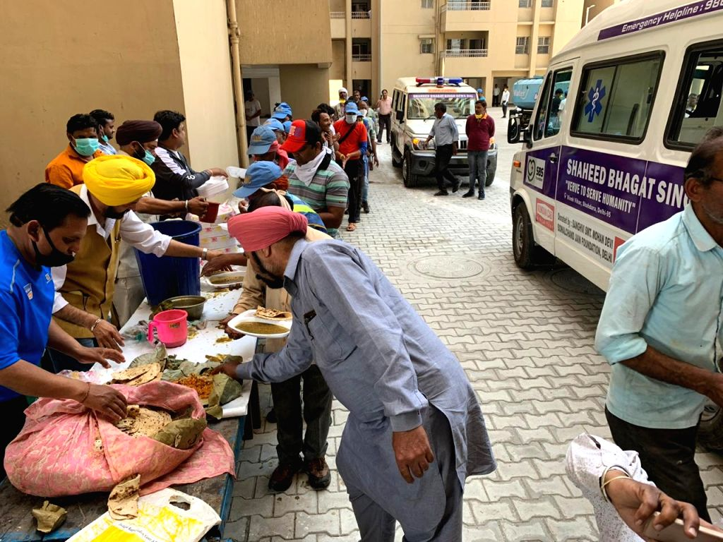Members of NGO Shaheed Bhagat Singh Sewa Dal (SBS Foundation) serve 'langar' to the workers engaged in managing Delhi's largest quarantine facility center at Mandoli in East Delhi on March ...