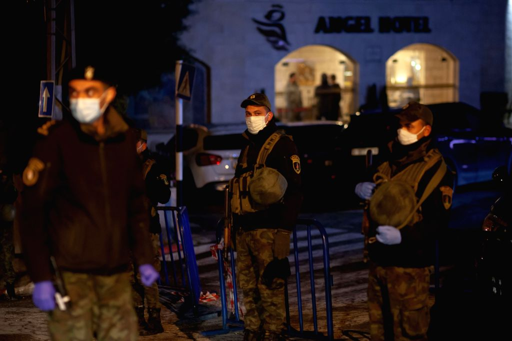 Members of Palestinian security forces stand guard outside a hotel under quarantine due to the COVID-19 outbreak, in Beit Jala, near the West Bank city of ...