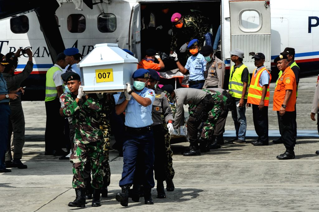 Members of Search and Rescue (SAR), Indonesian National Armed Forces (TNI) and policemen carry a coffin containing a victim of the crashed ATR 42-300 Trigana Air Services plane from a plane ...