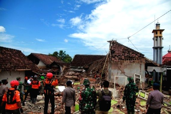 Members of search and rescue team are seen near damaged houses after a 6.1 magnitude quake hit Majang Tengah village in Malang, East Java, Indonesia, April 11, 2021.