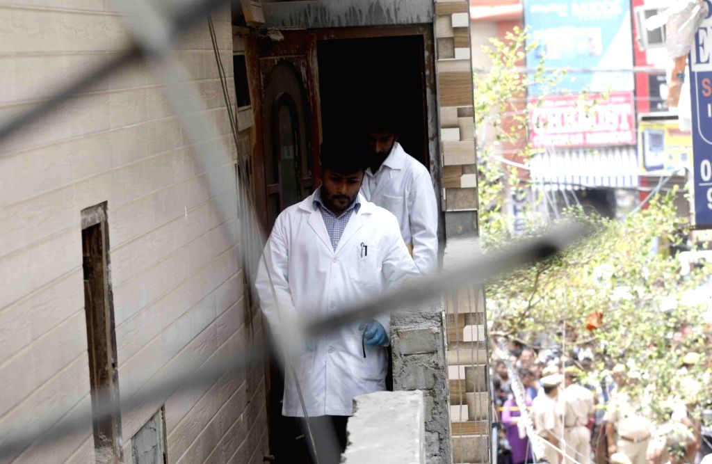 Members of the forensic team carry out investigation at the site where 11 members of a family were found deadsome blindfolded and hanging from an iron grill ceilingat their home, ...