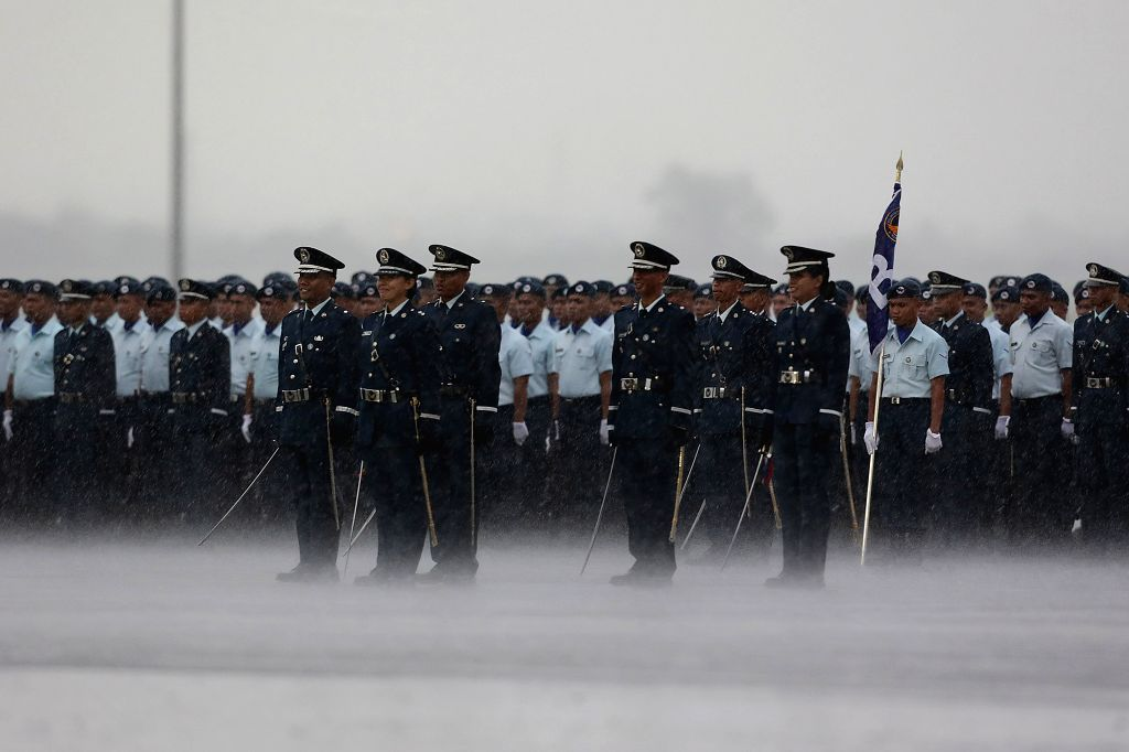 Members of the Philippine Air Force (PAF) brave the heavy rain during the 70th anniversary of the PAF at Clark Air Base in Pampanga Province, the ...