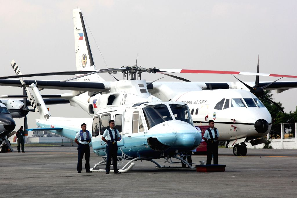Members of the Philippine Air Force (PAF) stand beside newly-acquired Bell-412EP helicopters during a turnover ceremony at Villamor Air Base in Pasay City, the ...