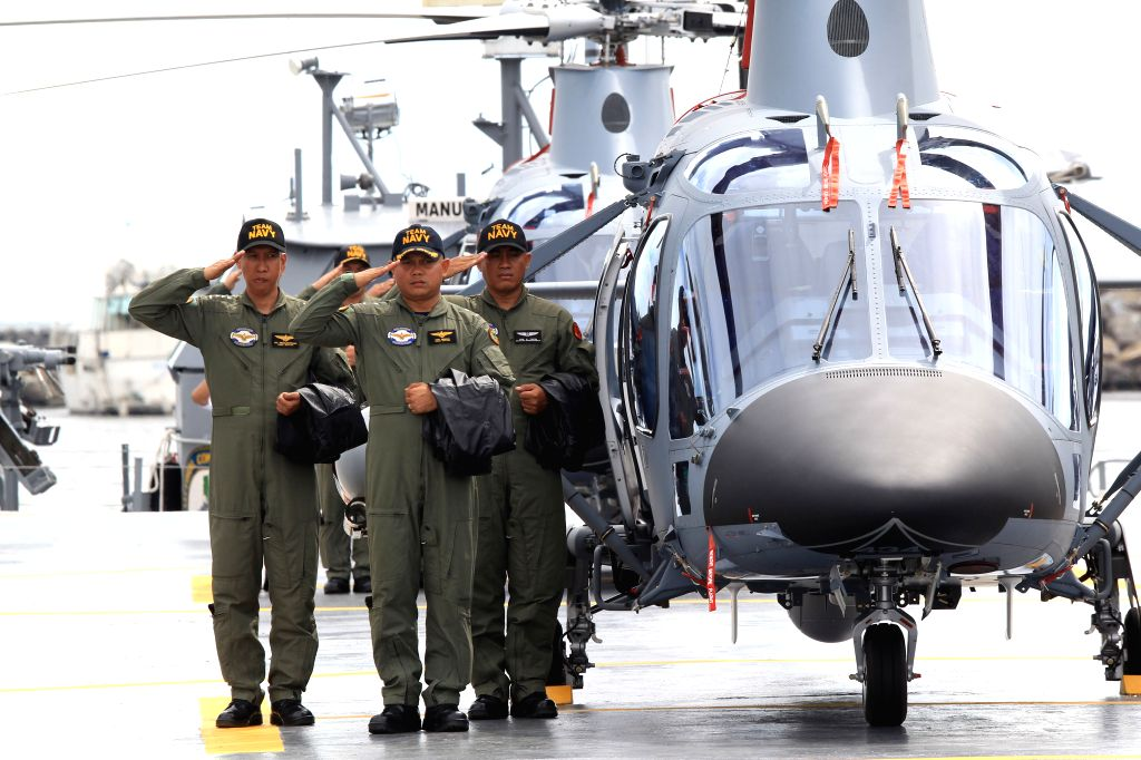 Members of the Philippine Navy stand beside one of the two newly-acquired AW109 helicopters in Manila, the Philippines, Aug. 10, 2015.