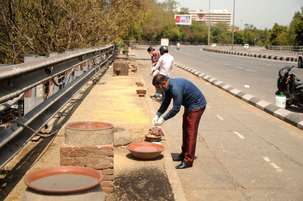Men keep food and water for birds at Jangpura Flyover on Day 6 of the 21-day nationwide lockdown imposed to contain the spread of coronavirus, in New Delhi on March 30, 2020.