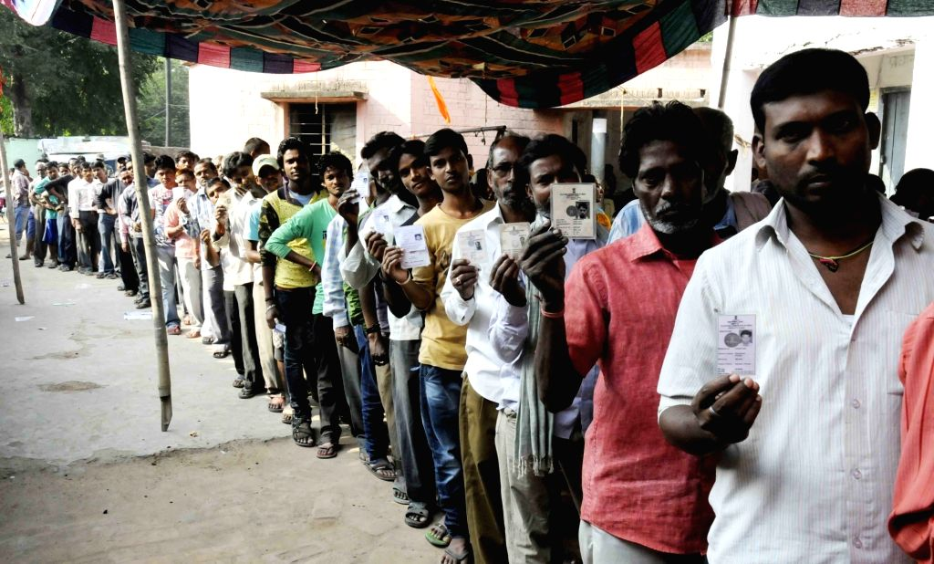 Men queue-up to cast his vote at a polling booth during the third phase of Bihar assembly polls in Patna on Oct 28, 2015.
