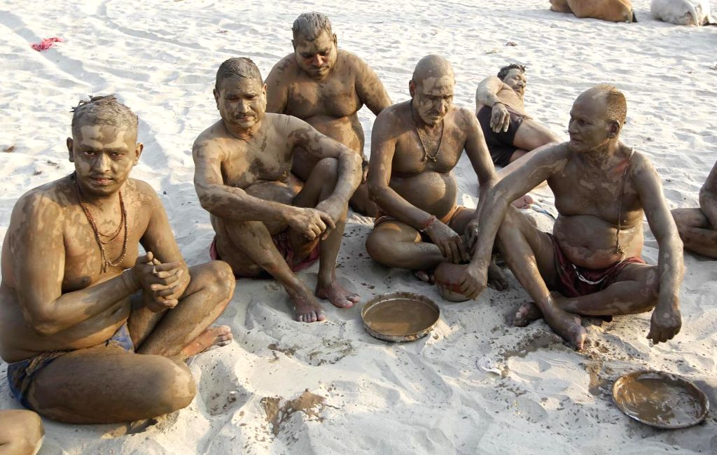 Men with mud applied on their bodies beat the heat on the banks of Ganga river in Allahabad, on June 13, 2017.
