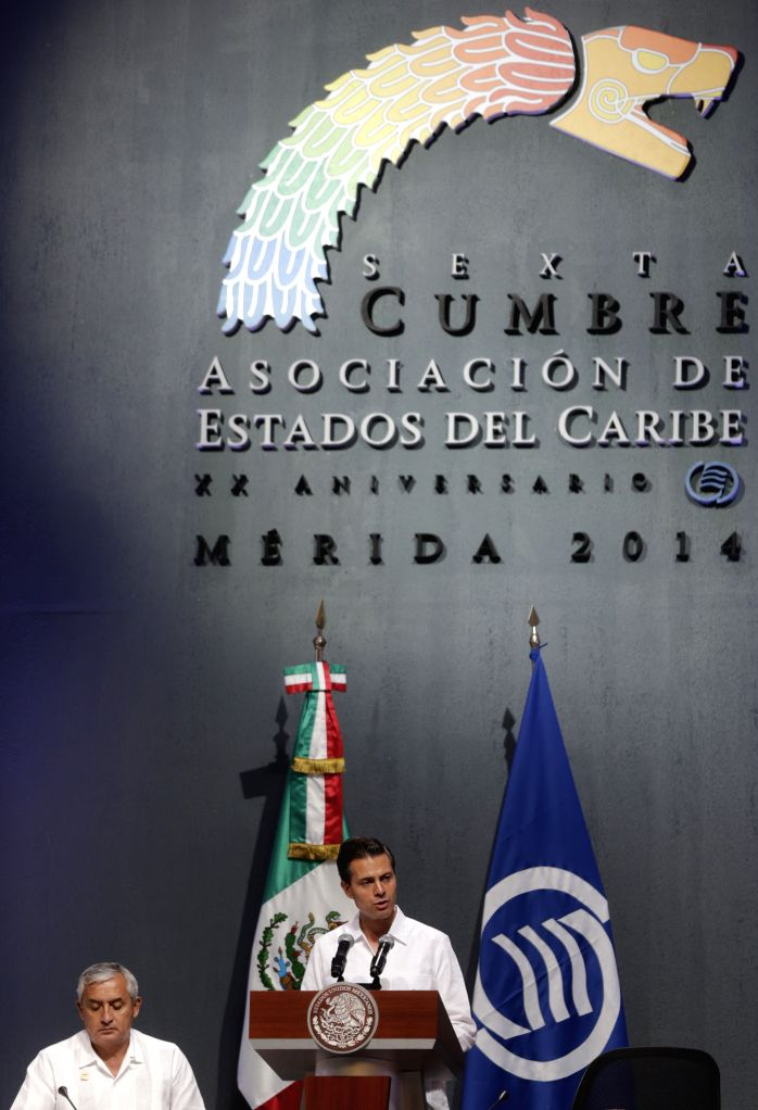 President of Mexico Enrique Pena Nieto (R) delivers a speech during the opening ceremony of the sixth Association of Caribbean States Summit in Merida, Yucatan, ...