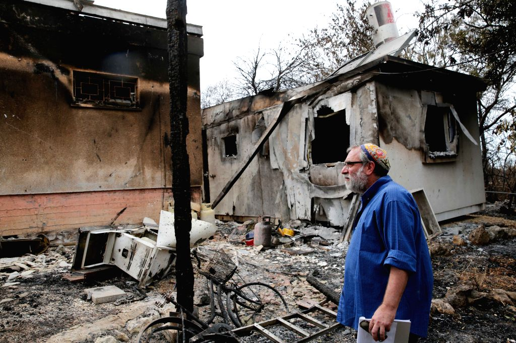 MEVO MODI'An Israeli man checks his burnt-down house following a fire amidst extreme heat wave in the village of Mevo Modi'im, Israel, on May 26, 2019. (Xinhua/Gil Cohen ... - Mevo Modi