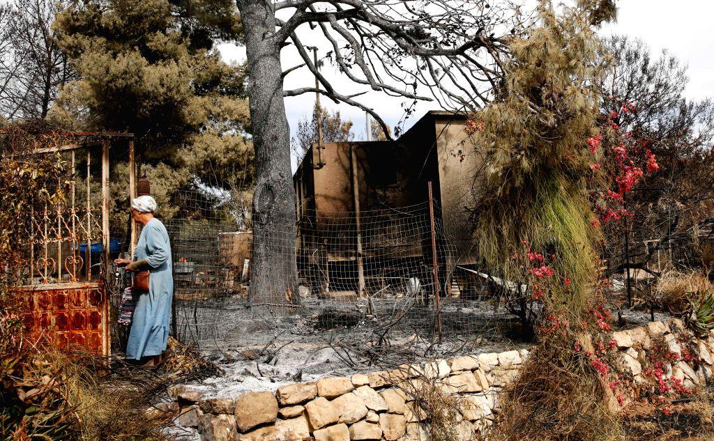 MEVO MODI'An Israeli woman checks her burnt-down house following a fire amidst extreme heat wave in the village of Mevo Modi'im, Israel, on May 26, 2019. - Mevo Modi