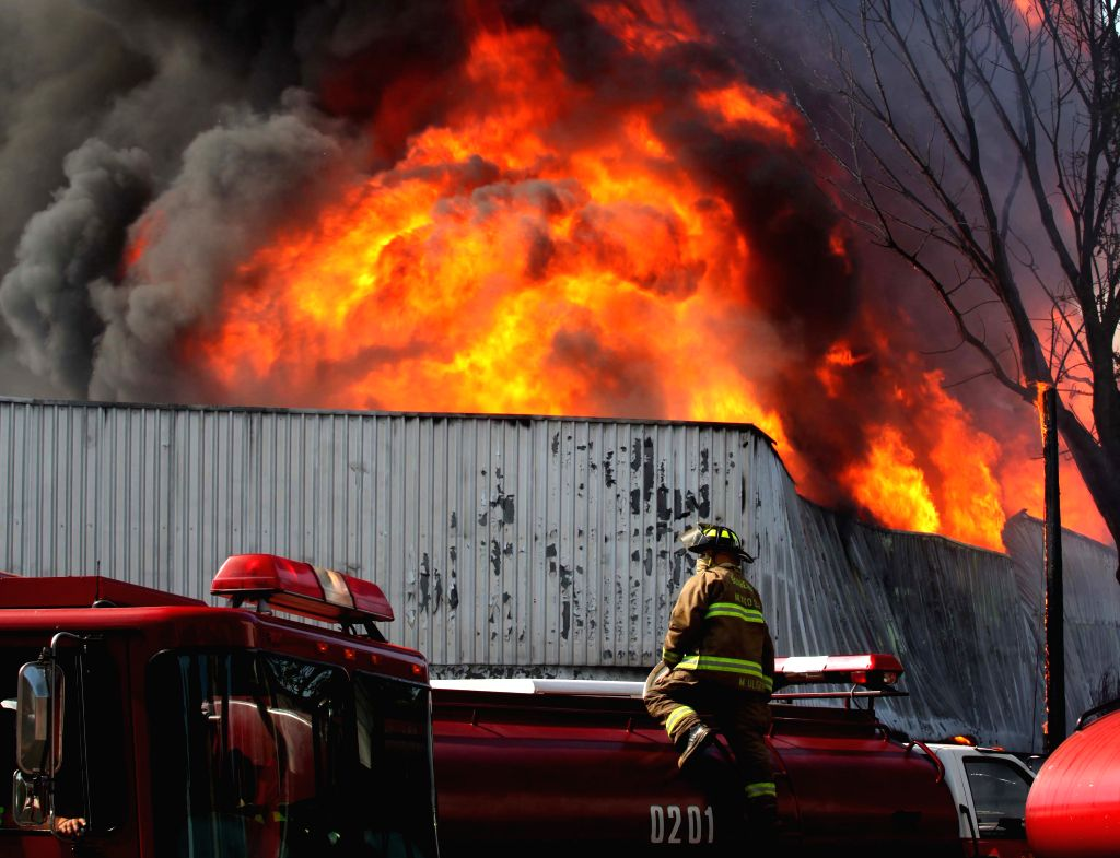 """Firefighters work in the fire site inside the storage area of the beer company """"Cerveceria Modelo"""" in Mexico City, capital of Mexico, on April 19, ..."""